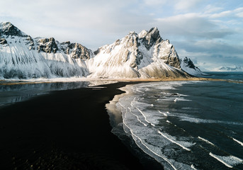 Aerial of Stokksnes beach in Iceland during winter and sunset with mountain in background