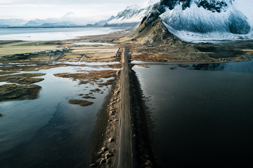 Aerial of Stokksnes beach with long road in Iceland during winter and sunset with mountain in background