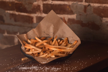 Crispy French Fries in a Basket with Sprinkled Salt