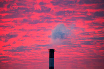 Steam rises from a smoke stack at sunset in Lansing, Michigan