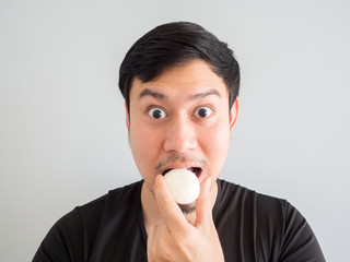 Close up of man is eating Mochi style snack.