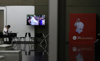 A television screen shows Pope Francis during his visit to Chile, prior to the Papal's arrival in Peru, at the media center in Lima