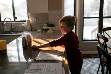 Lett, who suffers from Prader Willi Syndrome reaches for a snack in his home in Columbus
