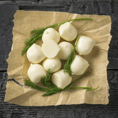 Freshly made mozzarella cheese with dill on a wooden table. Selective focus. The view from the top.