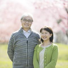 桜の前で微笑むシニア夫婦