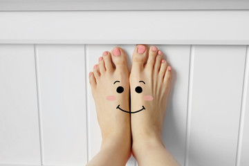 Smiley Face Barefoot with Pink Nail Polish Manicure. Beautiful Female Feet with White Headboard Bedroom Background Great for Any Use.