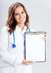 Female doctor showing blank clipboard, on grey
