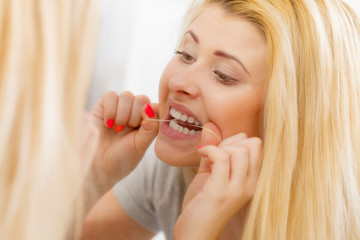 Woman cleaning her teeth using dental floss
