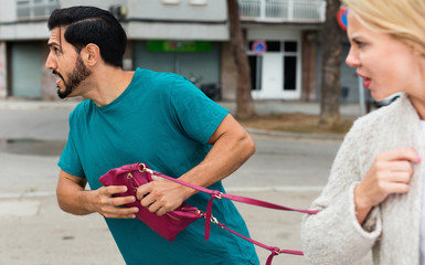 Man is stole the handbag from stranger woman