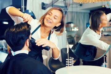 female professional shaving male's hair