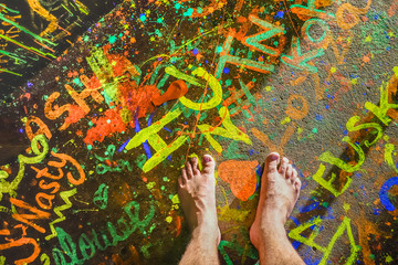 Naked human barefoot on fluo neon painted floor at full moon beach party in Thailand - Travel wanderlust concept with bare feet of guy having fun at event concert nightlife