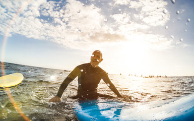 Wall Mural - Guy surfer relaxing on surfboard at sunset in Tenerife with unrecognizable people at surf boards on background - Sport travel concept with shallow depth of field with drops on lens as composition