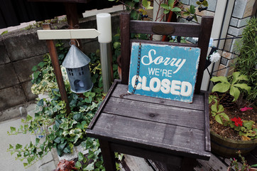 Closed Sign (Sorry we are Closed) Blue Metal Board Lean Against on Wooden Chair among Pot of Plant in Black and White