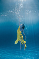 underwater picture of attractive young woman in dress swimming in swimming pool