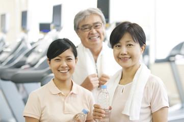 スポーツジムで水を持ち微笑む家族