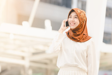 Portrait happy muslim young woman using mobile phone in city