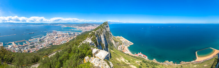 Panorama of top of Gibraltar Rock, in Upper Rock Natural Reserve: on the left Gibraltar town and bay, La Linea town in Spain at the far end, Mediterranean Sea on the right. United Kingdom, Europe.