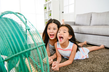 little girl with mother playing electric fan