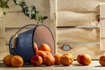 PEACH IN BLUE BUCKET. STILL LIFE FOOD FRUIT ON WOOD BACKGROUND