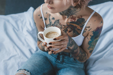cropped view of tattooed girl with pink hair drinking coffee in bed at morning