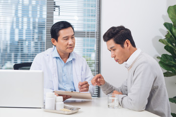 Doctor explaining prescription to male patient, healthcare concept