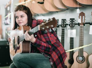 Smiling teen girl examining various acoustic guitars