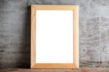 wooden frame on a wooden table on a gray wall. Template layout for adding a design or an inscription