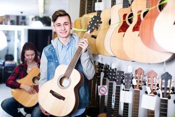 Teenagers examining guitars in shop