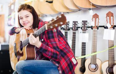 Teenage girl choosing acoustic guitar