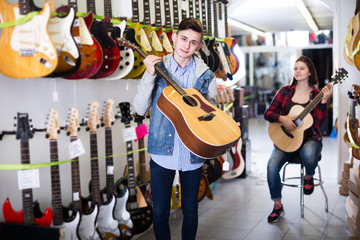 Teenagers examining guitars in shop