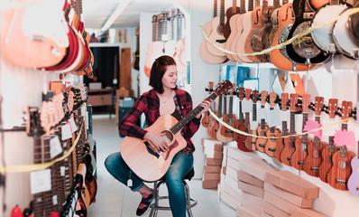 Smiling female teenager examining various acoustic guitars