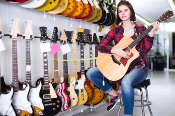 Female rock-n-roll player is deciding on acoustic guitar