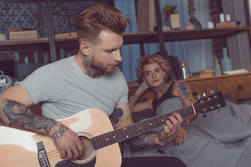 tattooed boyfriend playing on acoustic guitar for his girlfriend at home