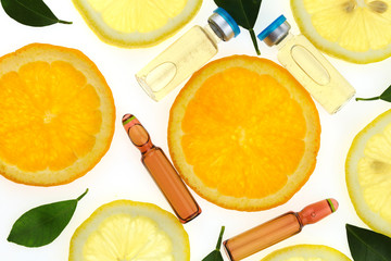 Vitamin C.ampoules with vitamin c and pieces of citrus fruit . Health and Beauty