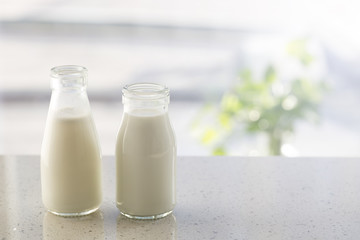 Two bottles of milk on table.