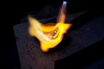 Goldsmith Gavriel Touboul melts pieces of silver into an ingot using a blowtorch, in his workshop in Jerusalem