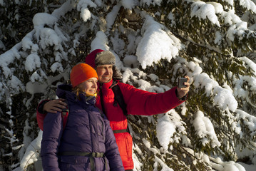 two people - man and woman - take pictures of themselves with a smartphone against the background of snow-covered fir branches outdoors in winter