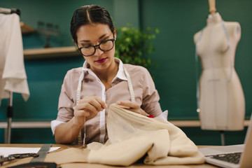 Female fashion designer doing handwork on dress