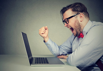 Angry man shouting at laptop