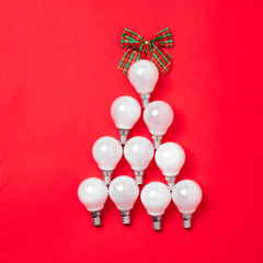 The christmas tree from lantern lamps laying on red background with copy space.