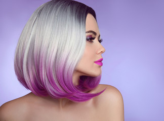 Colorful dyed Ombre hair extensions. Fashion haircut. Beauty Model Girl blonde with short bob purple hairstyle isolated on purple background. Closeup woman portrait.