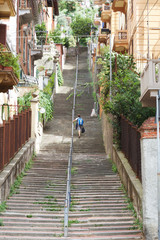 Boy is climbing stairs in la spezia Italy with mediterranean houses