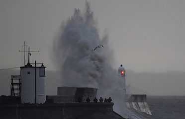 People watch as large waves and high winds associated with Storm Ffion hit the seawall and lighthouse at Porthcawl in south Wales