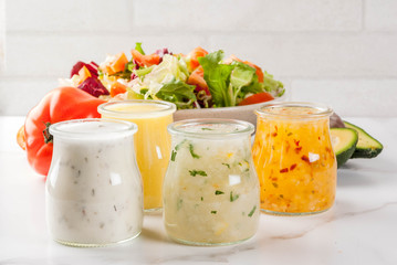Set of classic salad dressings - honey mustard, ranch, vinaigrette, lemon & olive oil,  on white marble table, copy space