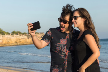 Young couple taking picture selfie smiling on the beach with cellular phone in the summer sun