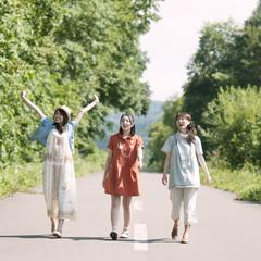 一本道を歩く3人の女性