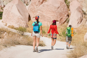 group of travelers walking by path trail in deserted landscape