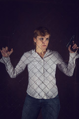 Woman with short hair holding a gun standing behind bars.