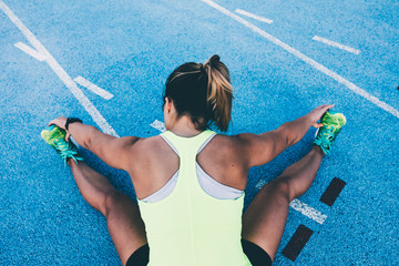 Fit Woman stretching on blue running track before run