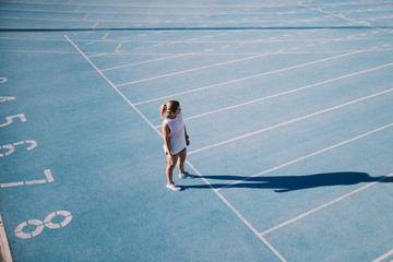 Young female athlete on blue running track